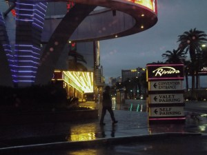 guy walking by Riv siign in rain