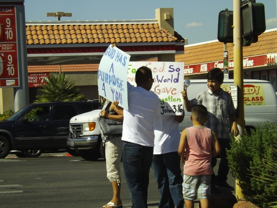The family that holds signs together. This family was proclaiming God's love of everyone on a Vegas street corner Saturday _ Photo by Royal Hopper