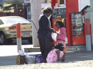 Mom and girls waiting for someone on a Sin City bus stop _ Photo by Royal Hopper