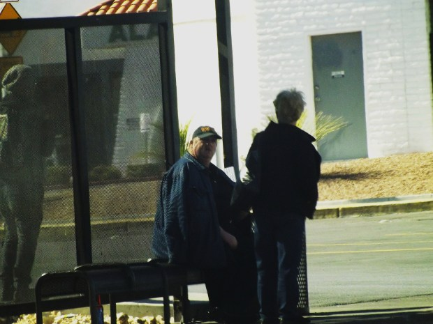 people talking at bus stop