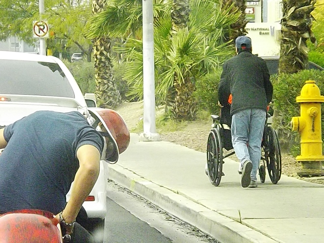 guy pushing wheelchair and motorcycle guy 2